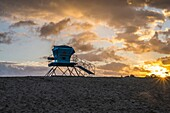 Sun rising on the horizon and a lifeguard tower on Ponto Beach. Carlsbad, California, United States.