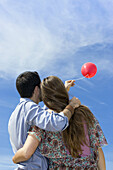 .Young couple flying red balloon. Marbella, Spain.