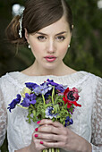 Young bride with wild flowers bouquet.
