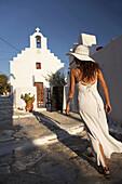 Woman walking towards a chapel, Amorgos, Cyclades Islands, Greek Islands, Greece, Europe.