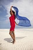 Woman with red dress on the beach, Jambiani, Zanzibar, Tanzania, East Africa.