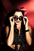 Beautiful Hispanic brunette model in pin-up style fashion with hair bow and dark sunshades. Accessorize.