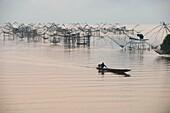 Shore-operated lift net, fishermen on boat at sunrise, Phatthalung, Thailand