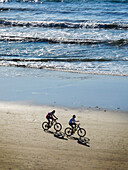 Early morning sunlight throws the shadows of two bicycle riders at Crystal Cove in Newport Beach, CA. Note heavy surf.