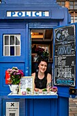 1937 traditional police box, transformed into a coffee shop, Merchant City, Glasgow, Scotland, UK. Picture includes the owner Laura Cameron.