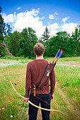 Young adult male with archery gear outdoors This high school senior portrait shows the archer enjoying his recreational sport