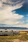 Two vintage Airstream trailers parked in a vast, dry landscape with blue sky and clouds above