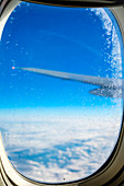 Blue sky and clouds, ice crystals on plane window flying over eastern Europe