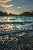 The sun rises as soft waves brush the shoreline of upper Twin Lake in Lake Clark National Park & Preserve, Alaska.