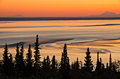 Swirling patterns in the mudflats at low tide and sunset, with Mt. Iliamna and Mt. Redoubt on the horizon, Turnagain Arm, Southcentral Alaska