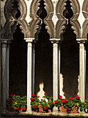 'Decorative pillars and a facade of a building with red flowers lining a ledge; Amalfi, Campania, Italy'