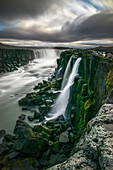 'Waterfall flowing over moss covered cliffs; Selfoss, Iceland'