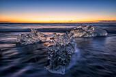 'Waves break around icebergs on the southern shore of Iceland, near the glacial lagoon of Jokursarlon; Iceland'