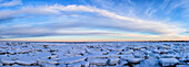 'Ice forms on the shores of Hudson Bay as sunset starts to light up the clouds; Churchill, Manitoba, Canada'