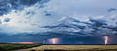 'Storm clouds and lightning strikes over a rural landscape; Thunder Bay, Ontario, Canada'