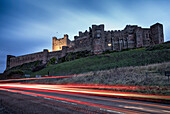 'Light trails on the road and Bamburgh Castle; Bamburgh, Northumberland, England'