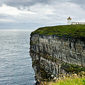 'Duncansby Head Lighthouse on the edge of a cliff on the coast under a cloudy sky; Scotland'