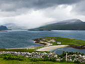 'A beach and green landscape with low clouds over the mountains in the distance; Scotland'