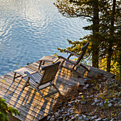 'Two wooden lounge chairs on a dock looking out at Lake of the Woods at dusk; Ontario, Canada'