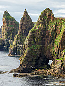 'Rugged peaked cliffs and a natural arch along the coastline; John O'Groats, Scotland'