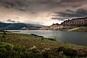 'The water and rock cliffs of Blue Mesa Reservoir with moody clouds and interesting light; Gunnison, Colorado, United States of America'