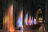 'Light streaming through stained glass windows with colourful light columns along the cathedral nave, altarpiece in St. Mary's Chapel visible background; Washington, District of Columbia, United States of America'
