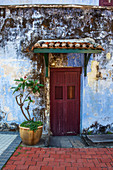 'A faded red door sits surrounded by a weathered blue wall in downtown Georgetown; Georgetown, Penang, Malaysia'