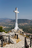 'Walkway with railing to a large, white stone cross with mountains in the distance; Jaen, Spain'