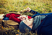 'A young couple laying in the grass and holding hands in a park in autumn; Edmonton, Alberta, Canada'