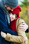 'A young couple holding each other closely in a city park in autumn; Edmonton, Alberta, Canada'