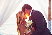 Beautiful Sunset Wedding by the Sea. Bride and Groom Kissing at Sunset. Romantic Married Couple.