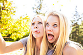'Two sisters having fun outdoors in a city park in autumn taking selfies of themselves and making funny faces; Edmonton, Alberta, Canada'