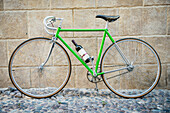 'Green bicycle with bottle of wine; Alghero, Sardinia, Italy'