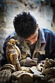 'A man hand carves figurines; Bethlehem, Jerusalem'