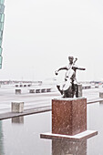 'A statue of cellist Erling Blondal Bengtsson by sculptor Olof Palsdottir sits outside the Harpa Public Concert Hall, snow falling and covering the statue; Reykjavik, Iceland'