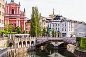 'The Slovenian capital city of Ljubljana, with a footbridge over a tranquil canal; Ljubljana, Slovenia'
