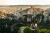 'Two friends having rest in the surroundings of Cuenca with a beautiful landscape behind them; Cuenca, Castile-La Mancha, Spain'
