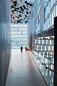 'Mother and daughter explore interior of the Harpa public concert hall, designed by the Danish firm Henning Larsen Architects and the Icelandic firm Batteriao Architects, the glass facade designed by Icelandic glass artist Olafur Eliasson; Reykjavik, Icel