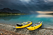 A pair of yellow inflatable kayaks on the Lower Twin Lake beach with a summer thunderstorm in the background, Lake Clark National Park & Preserve, Southcentral Alaska.