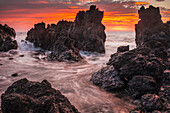 'The colours of sunrise behind coastal lava rocks; Laupahoehoe, Island of Hawaii, Hawaii, United States of America'