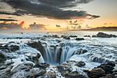 'Surf spills into a hole in a rock outcrop on the east side of Kauai; Kauai, Hawaii, United States of America'