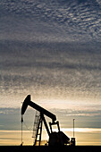 'Silhouette of a pump jack at sunrise with the sun glowing on the horizon and colourful clouds in the sky; Alberta, Canada'