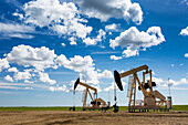 'Two pump jacks in a field with large puffy clouds and blue sky; Alberta, Canada'