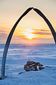 Whalebone arch frames the setting sun at the shore of the Arctic Ocean in Barrow, North Slope, Arctic Alaska, Winter
