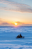 Two native Alaskans drive a snow mobile through a stark snow covered landscape at sunset, Barrow, North Slope, Arctic Alaska, Winter