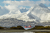 A Coast Guard ship passes behind rocks across from Dock Point at low tide, Prince William Sound, Valdez, Southcentral Alaska, winter