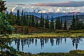 Scenic sunrise view over Mt. Brooks and the Alaska Range with a tundra pond in the foreground, Denali National Park, Interior Alaska, Autumn