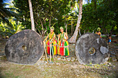 'These two young girls between the two pieces of stone money, are in a traditional outfit for cultural ceremonies on the island of Yap; Yap, Federated States of Micronesia'