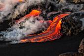 'Flowing lava and steam on a hawaiian island; Island of Hawaii, Hawaii, United States of America'