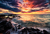 'Dramatic colourful sky at sunset over the pacific ocean and the rugged coastline of a hawaiian island; Hawaii, United States of America'